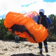 Stock Photo: Paraglider launching from ridge with orange canopy