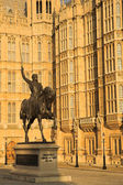 The buildings of the House of Parliament with a statue of Richard on his horse — Stock Photo