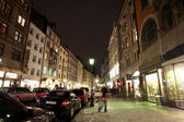 Buildings at night in Munich with walking on the sidewalks - movement. — Stock Photo