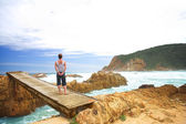 Woman facing the sea standing on a bridge — Stock Photo
