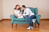 Woman and boyfriend sitting on couch, talking — Stock Photo