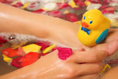 Plastic toy duck on a woman's foot in the bath. — Stock Photo