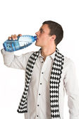 Man with white pinstripe shirt and scarf with bottled water in hand. — Stock Photo
