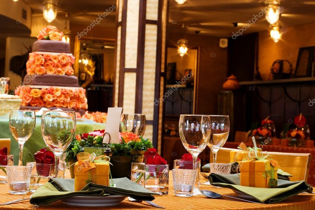 Ajuste de la tabla con copas de vino y un pastel en el fondo
