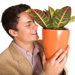 Businessman holding a pot plant — Stockfoto