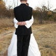 Bridal couple standing on a dirt road in an embrace - Stock Photo