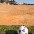 Dirty soccer ball on a rural football field — Stock Photo