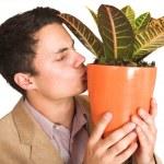 Businessman kissing a pot plant. — Stock Photo
