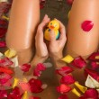 Nude woman in a bath, holding a plastic duck toy. — Stock Photo