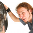 Royalty-Free Stock Photo: Man with blue shirt cooling down in front of a fan.