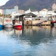 Cape Town waterfront harbor with three boats reflecting in the water and the City skyline in the background. — Stock Photo
