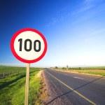 在一个阳光明媚的夏日签名旁边空路的最大速度限制警告标志或道路 — 图库照片