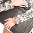 Picture of hands of a business woman dressed in a white shirt with black stripes. - Stock Photo