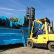 Yellow Forklift placing cargo on Flatbed truck for dispatch - ストック写真