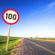 Warning sign or road sign for the maximum speed limit next to an empty road on a sunny summer day. — Stock Photo