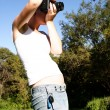 Woman with camera on nature - Stock Photo