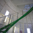 Green metal spiral staircase inside a white walled lighthouse — Stock Photo