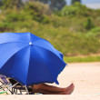 Man relaxing on the beach under a blue umbrella — Stock Photo #22128843