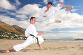 Young adult men with black belt practicing on the beach on a sunny day. — Stock Photo