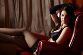 Sexy young adult caucasian woman in black lingerie sitting — Stock Photo