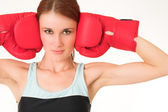 Sexy young adult Caucasian woman in a training wear with boxing gloves — Stock Photo