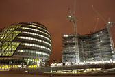 Office block and construction scene at nighttime. — Stock Photo