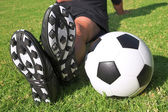 A male soccer (football) player, referee or coach sitting next to a soccer ball — Stock Photo