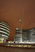 Office block and construction site at nighttime. — Stock Photo