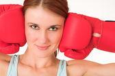 Una donna in abbigliamento palestra, indossa guanti boxe rossi. — Foto Stock