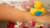 Foot of a woman with a plastic toy duck on it — Stock Photo