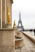 A golden statue in the foreground with the Eiffel Tower in Paris — ストック写真
