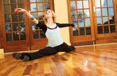 A Female Dancer practicing in her studio - in a split, on the floor — Stock Photo