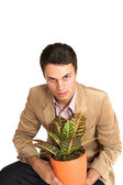 Businessman bending down, holding a pot plant. Copy space. — Stock Photo