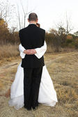 Bridal couple standing on a dirt road in an embrace — Stock Photo