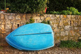 Old blue rowboat against a wall — Stock Photo