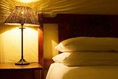 Interno della camera con lampade da comodino, letto in legno e copripiumino bianco — Foto Stock