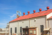 Corrugated iron building with red roof on mine premises with shaft winch in the background — Stock Photo