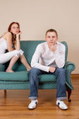Woman and boyfriend sitting on couch, looking bored — Stok fotoğraf