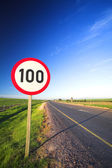 Warning sign or road sign for the maximum speed limit next to an empty road on a sunny summer day — Stock Photo