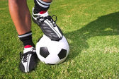 A male soccer (football) player, referee or coach standing with one foot on a soccer ball. — Stock Photo
