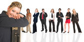 Beautiful blonde businesswoman standing in front of a group of business — Stock Photo