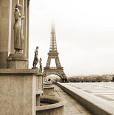 A golden statue in the foreground with the Eiffel Tower in Paris, France — Stock fotografie