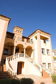 Orange and peach colored three storey mansion against a blue sky on a summer day. — Stock Photo