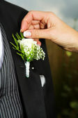 Close-up of Bridal accessories. Hand of bride fixing a Corsage. — Stock Photo