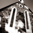 Catholic church building with a cross on the steeple - high key black and white, defocussed — Stock Photo