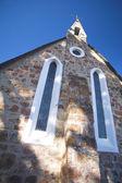 Katolická církev s křížkem na věž proti sunny modré oblohy — Stock fotografie