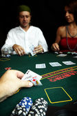 Ace of clubs and King of Diamonds in hand in a poker hand with high value chips on the table — Stock Photo
