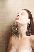 Sexy young adult Caucasian woman with long auburn hair and petite breasts taking a shower in a tile and glass modern bathroom. — Stock Photo