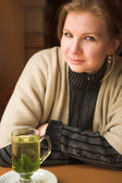 Blonde caucasian adult woman with hot mint tea next to a natural light window in the beginning of winter. — Stock Photo
