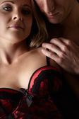 Young and fit caucasian adult couple in an embrace. Semi-nude and topless against a dark background with the woman wearing a sexy red and black lace corset.. — Stock Photo